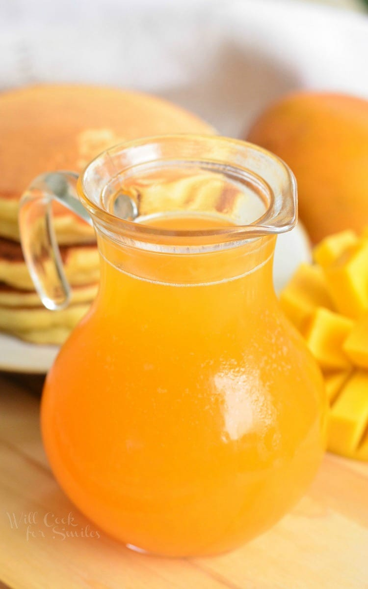 Homemade Mango Syrup in a glass with pancakes in the background