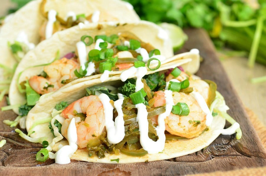 Tequila Lime Shrimp Tacos with sour cream and green onions on top