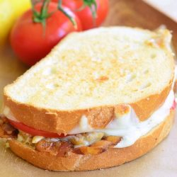 crab tomato and bacon grilled cheese sandwich stacked on a wax paper on a wooden serving tray with 2 vine ripe tomatoes in the background
