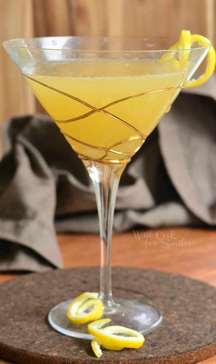 Pineapple Lemon Martini in a martini glass with a lemon peel twist as garnish sitting on a table