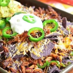 Baking sheet pan with pulled pork nachos topped with sour cream and sliced jalapenos on a wooden table with a white and yellow cloth in the background