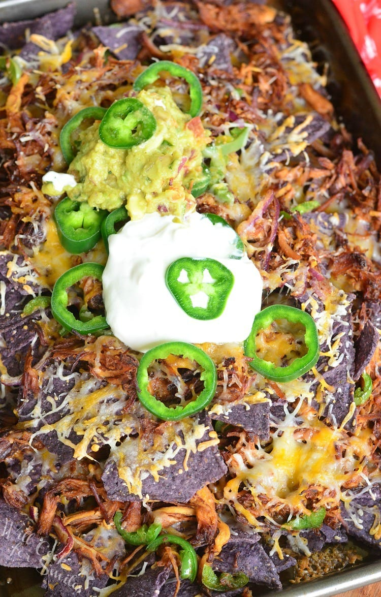 Pulled Pork Nachos on a baking sheet with sour cream on top and slices of jalapeno and guacamole