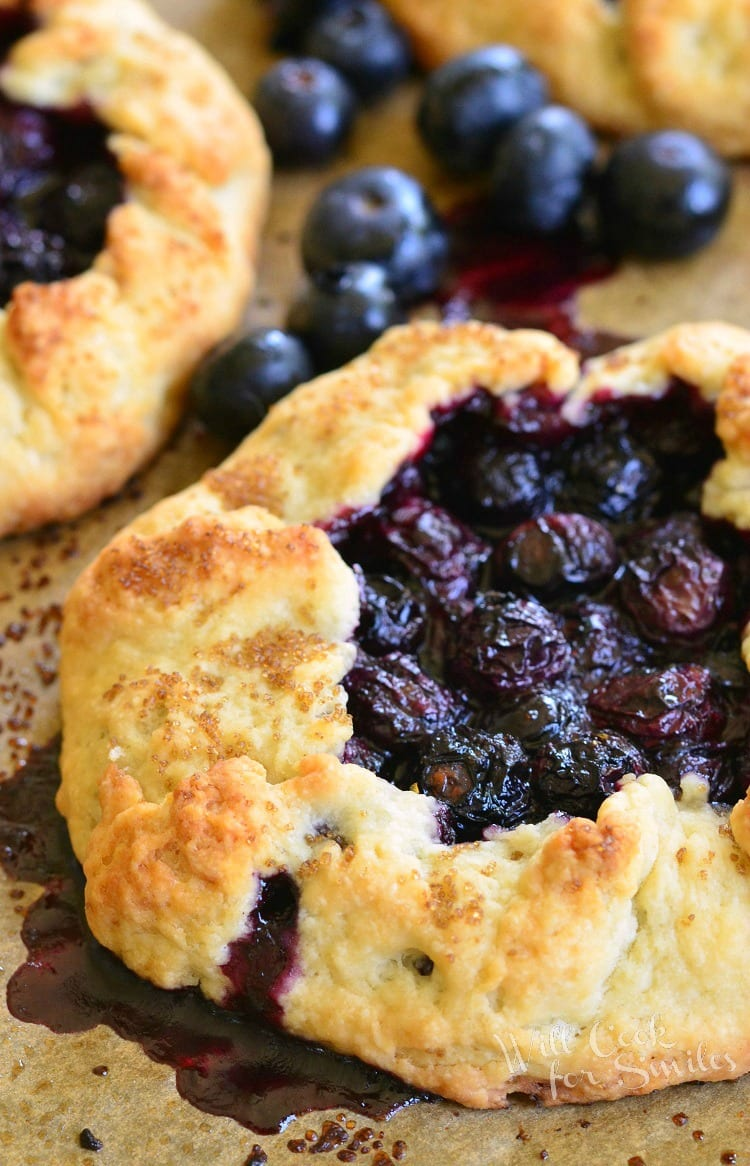 Blueberry Vanilla Lemon Galette on parchment paper with blueberries around it