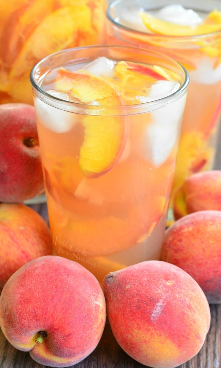 Ginger Peach and Honey Iced Green Tea in  glass with ice and peaches, sitting on a table with peaches around the glass