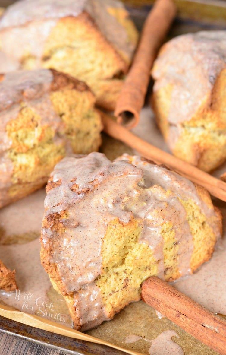 Glazed Cinnamon Swirled Scones on a baking sheet with cinnamon sticks around it