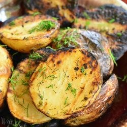 Herbed grilled potatoes on a brown and white platter on a wooden table topped with dill