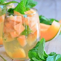 2 glasses filled with melon mint wine spritzer topped with mint leaves on a wooden table as viewed close up
