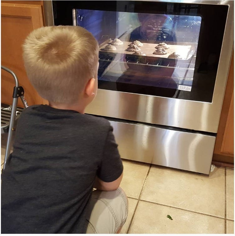 my little man sitting in front of the oven watching the cookies inside bake