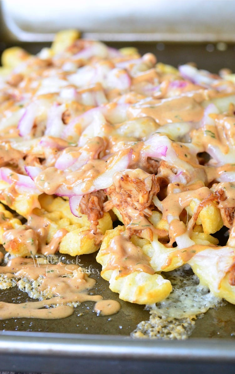 BBQ Ranch Chicken Loaded Fries with chicken, cheese, and red onions on a baking dish