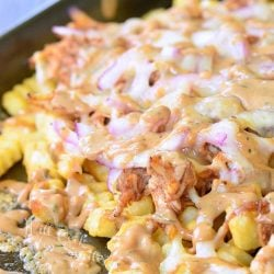 BBQ ranch chicken loaded fries on a baking tray loaded with toppings