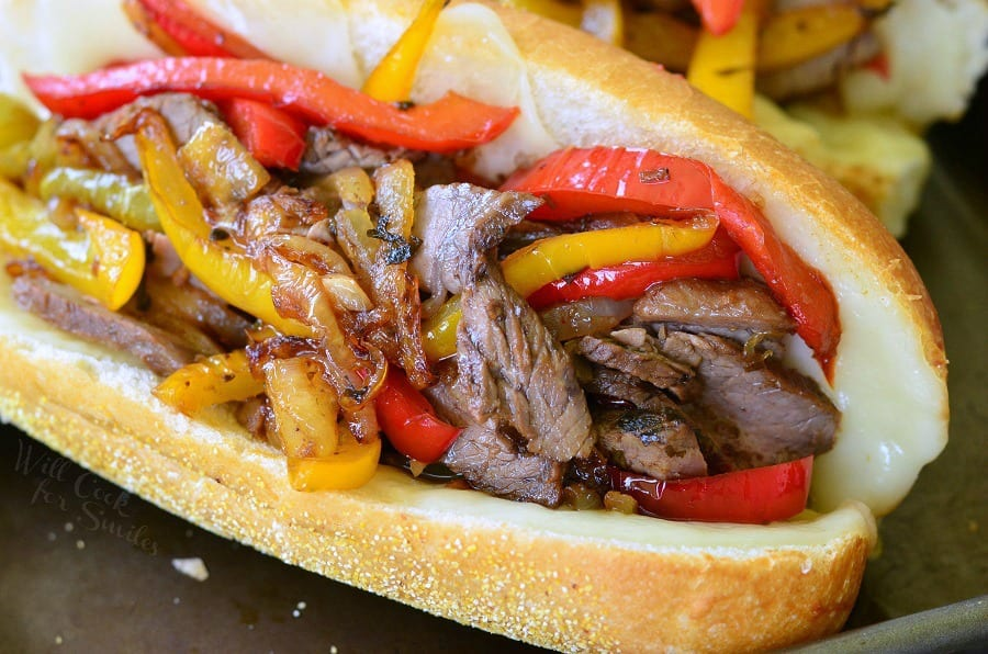 horizonal imagine of Fajita Philly Steak Sandwich with steak, red and yellow bell peppers, with onions on a hoagie roll