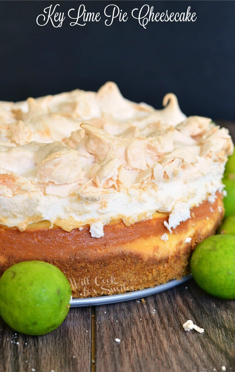 Key Lime Pie Cheesecake with meringue on top on a table with limes