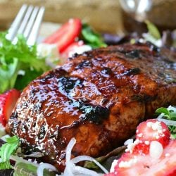 Strawberry balsamic glazed baked salmon salad with a fork to the left and a glass container of balsamic dressing in the background