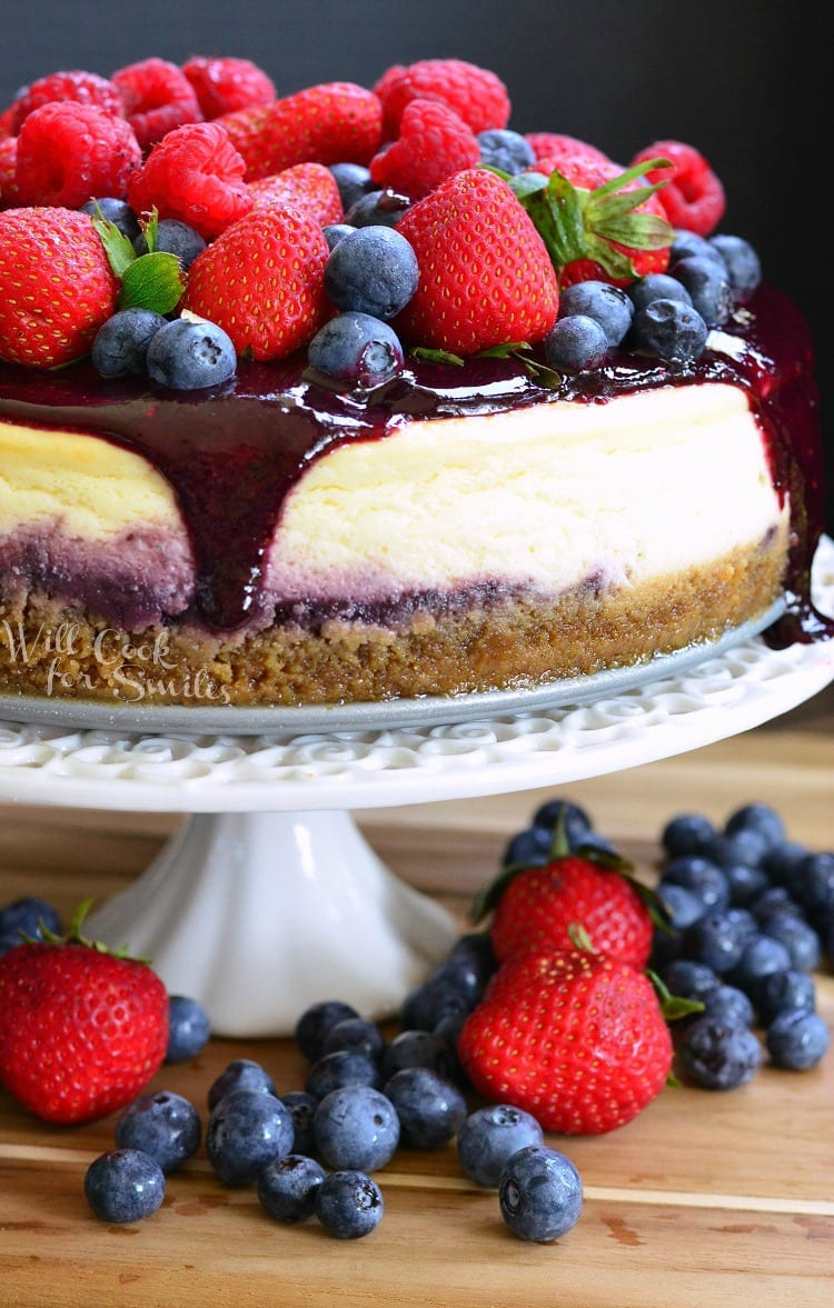 cheesecake with berry sauce, strawberries, blueberries, and raspberries on top on a white cake stand with blue berries and strawberries under it on a wood table