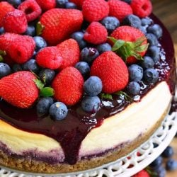 Whole mixed berry cheesecake on a cake platter with berries below the platter as well as viewed close up