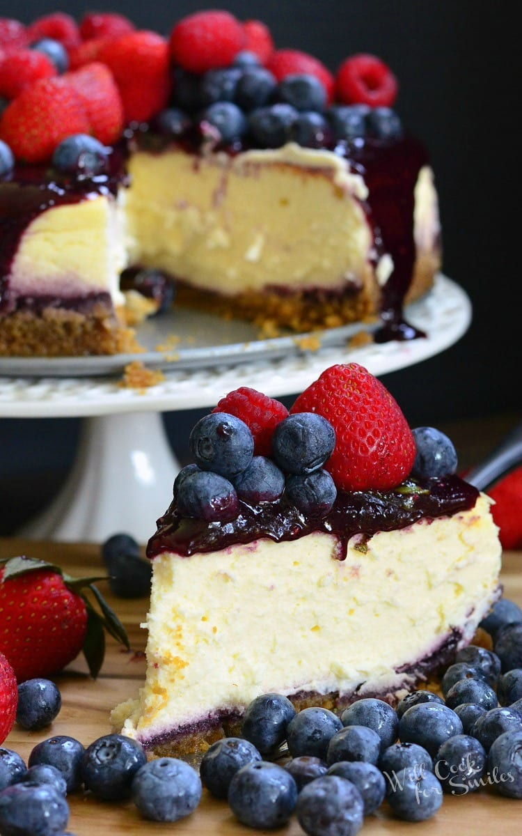slice of cheesecake with berry sauce, raspberries, and strawberries on top on a cutting board with strawberries and blueberries around it with the rest of the cheesecake on a white cake stand in the background