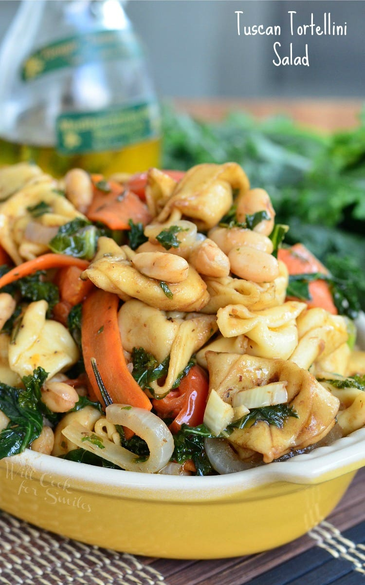 Tuscan Tortellini Salad with carrots, onions, and spinach in a yellow bowl