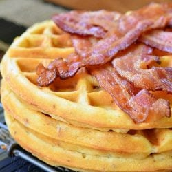 Savory waffles stacked on a metal rack with strips of bacon piled on top of top waffle