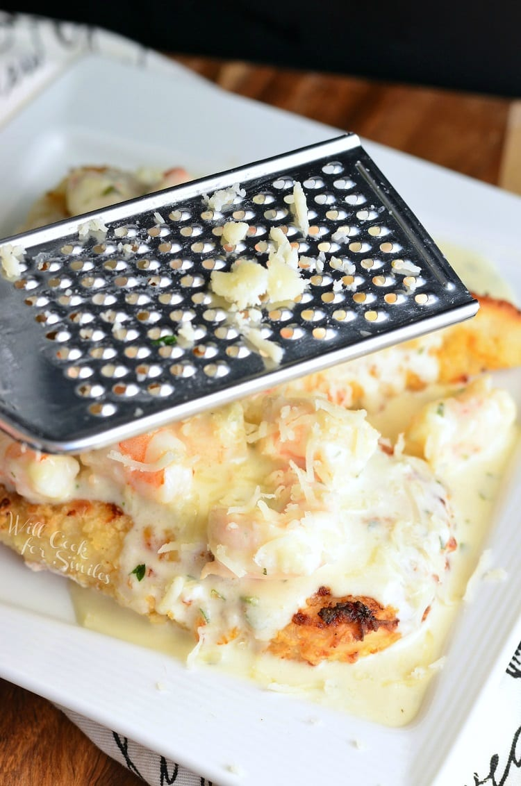 grating cheese with a cheese grater over Oven Fried Chicken topped with shrimp and a Creamy Fontina cheese Shrimp Sauce on a white plate