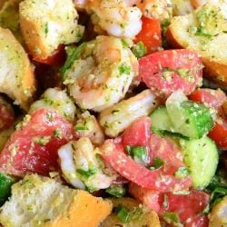 Wooden bowl filled with panzanella salad with shrimp and pesto on a tan placemat as viewed from above and close up