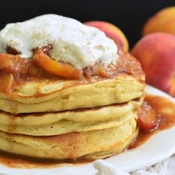 Stack of peaches and cream fluffy buttermilk pancakes on a white decorative plate with peaches in the background as viewed close up