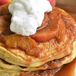Stack of peaches and cream fluffy buttermilk pancakes on a white decorative plate with peaches in the background