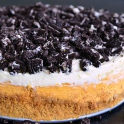 Layered Oreo Pumpkin Cheesecake on a black table as viewed close up