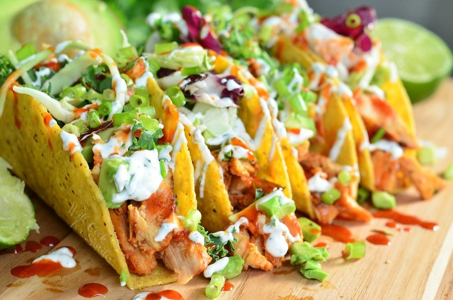 Hard shelled Chicken Tacos with avocado, sour cream, green onions and siracha