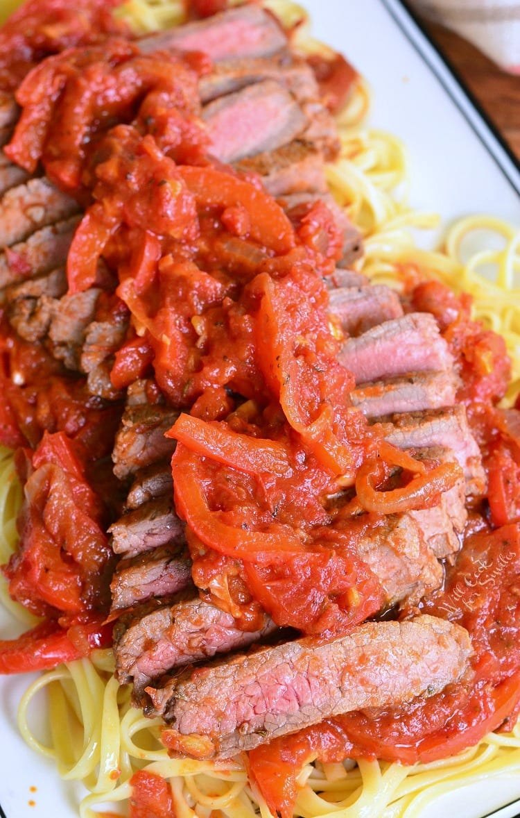 Steak Pizzaiola Linguine on a plate with onion and tomato sauce on top