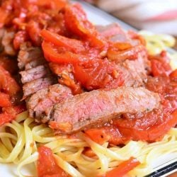 decorative white rectangular plate with steak pizzaiola linguine on a wooden table as viewed close up