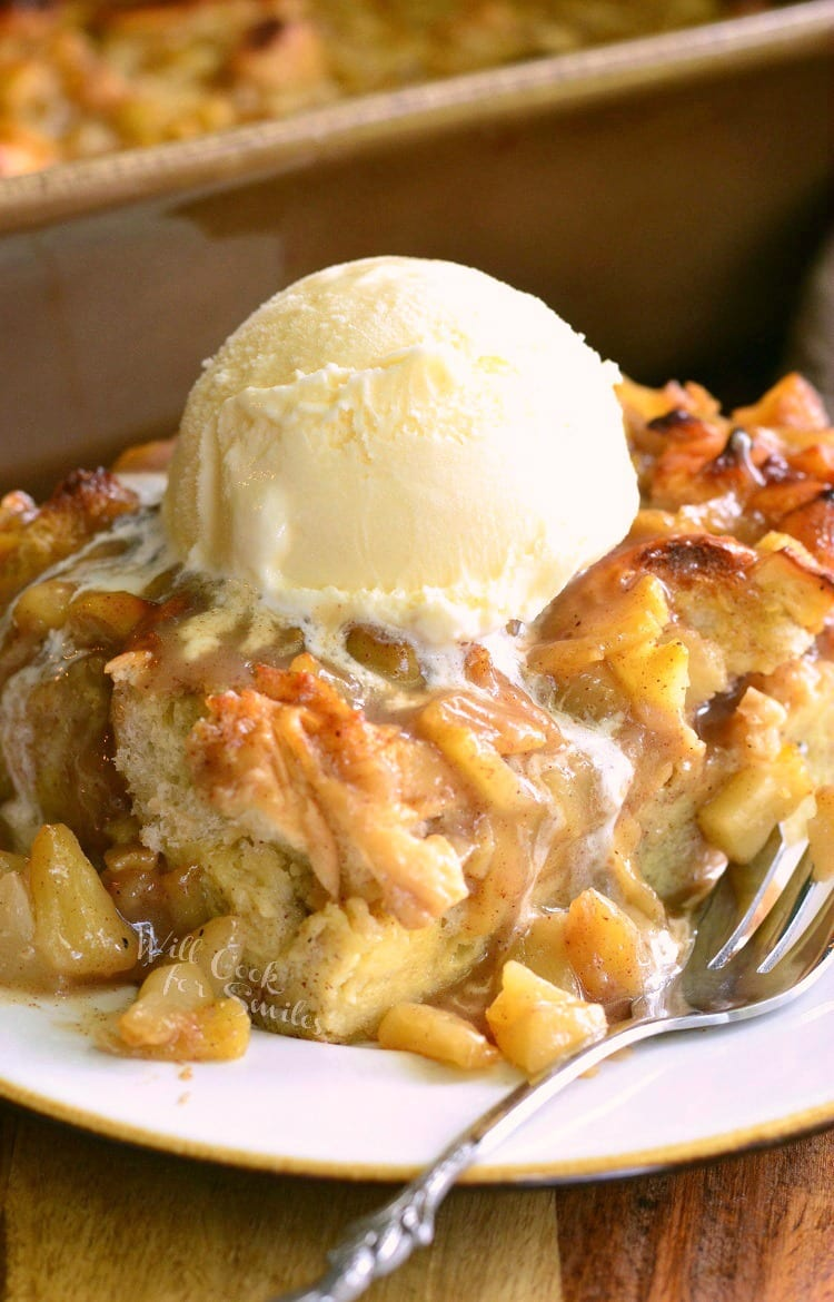 Apple Pie Bread Pudding with ice cream on top on a white plate with a fork to the right