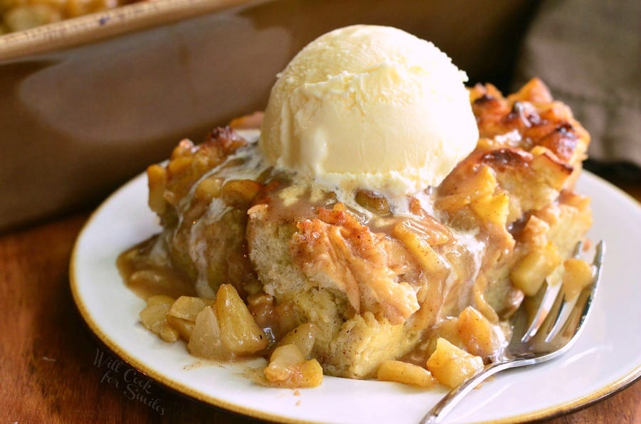 Apple Pie Bread Pudding on a white plate with a scoop of vanilla ice cream on top with a fork to the right