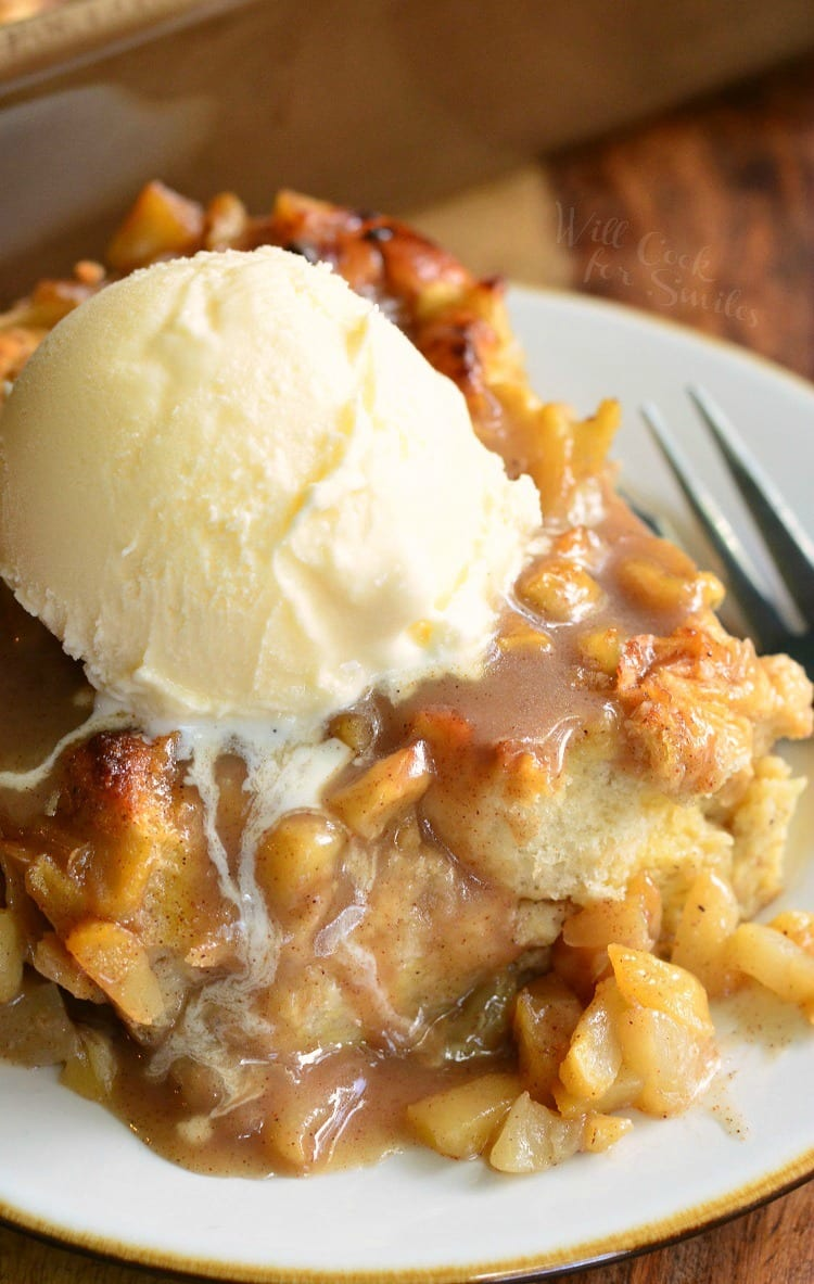 Apple Pie Bread Pudding with a scoop of vanilla ice cream on top on a white plate with a fork to the right
