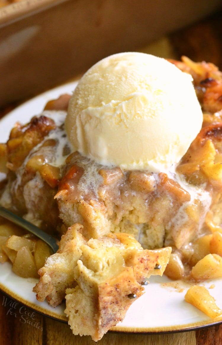 Apple Pie Bread Pudding with a scoop of vanilla ice cream on top with a scoop on a fork to the left