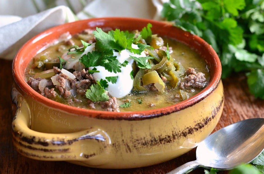 horizonal view ground Beef and Poblano Enchilada Soup. hamburger with poblano peppers in a soup bowl with sour cream and cilantro on top