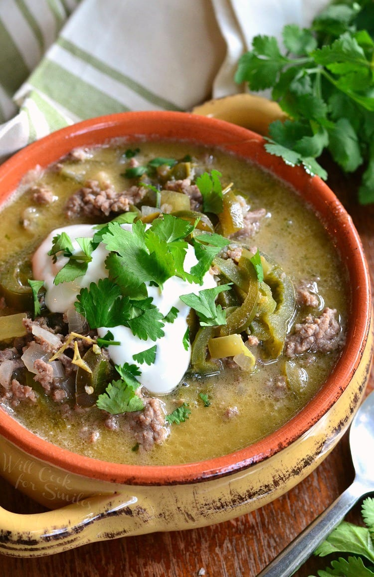 top view of Beef and Poblano Enchilada Soup ground beef with poblano peppers in a soup bowl with sour cream and cilantro on top