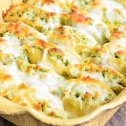 Cream colored baking pan with cheesy pesto chicken stuffed shells as viewd from slightly above and close up.
