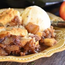 Large black skillet filled with maple pecan apple cobbler on a wooden table in the background with one portion on a decorative tan plate and topped with ice cream.