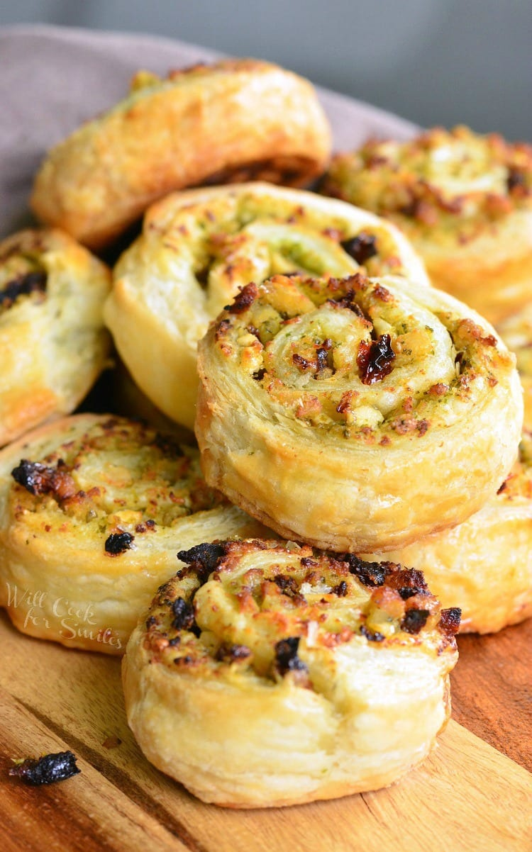 Pesto Chicken Pinwheels - Flaky pastry, juicy chicken, fresh pesto, sun dried tomatoes, and feta cheese rolled together to create a snack to delight your taste buds.
