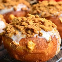 cheesecake pumpkin doughnuts with gingersnap crumb topping on a wire rack resting on a wooden table as viewed close up.