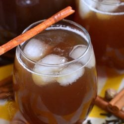Glass filled with spiced iced tea with an additional glass and a pitcher filled with spiked tea in the background