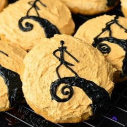 """Decorative cookies in the design of """"The Nightmare Before Christmas"""" on a cooling rack as seen from above."""