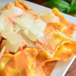 decorative white square plate filled with ravioli in creamy red pepper sauce topped with shaved parmesan.