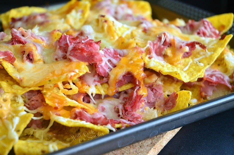 horizonal photo of Tortilla chips, corn beef, and cheese on a baking sheet