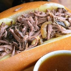 large hogie roll covered in cheese filled with slow cooker mushroom and onion italian beef on a wooden table as viewedclose up.