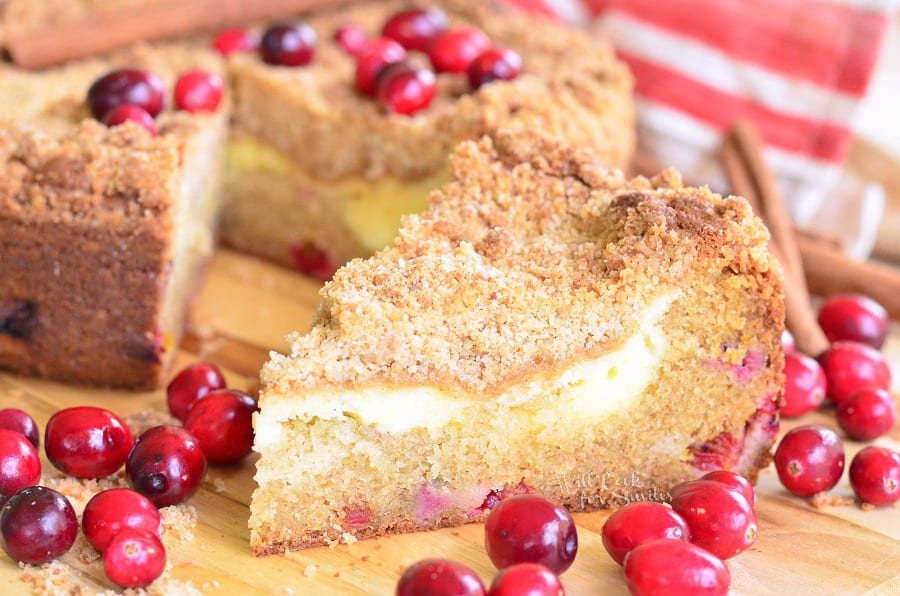 a slice of Cranberry Cream Cheese Coffee Cake surrounded by cranberries on a cutting board with the rest of the cake in the background