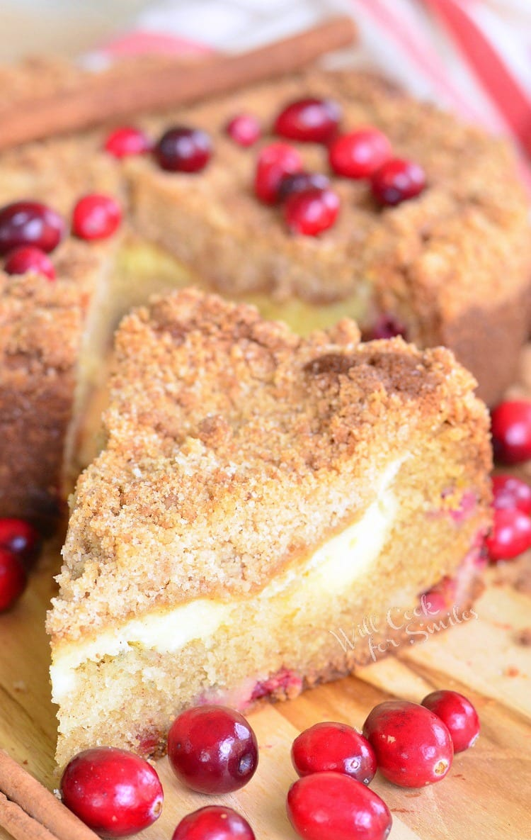 A slice of Cranberry Cream Cheese Coffee Cake on a cutting board with the rest of the cake in the background