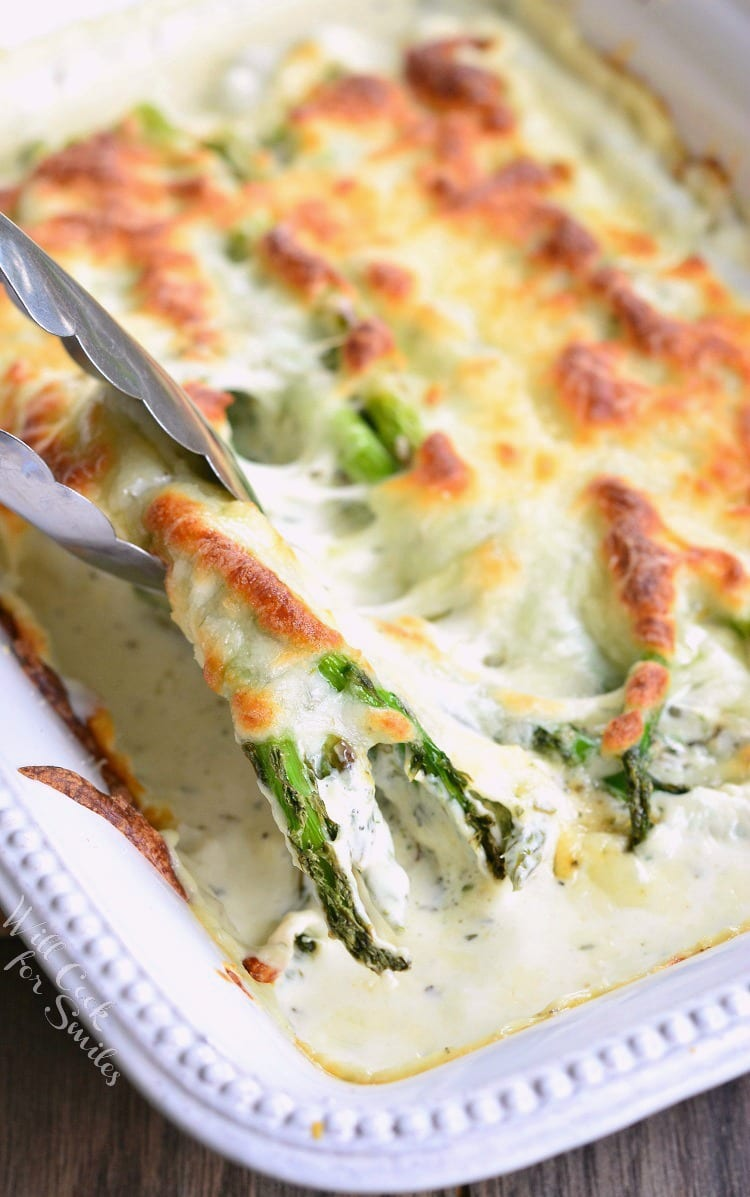 Italian Asparagus in a white casserole dish with tongs lifting some out