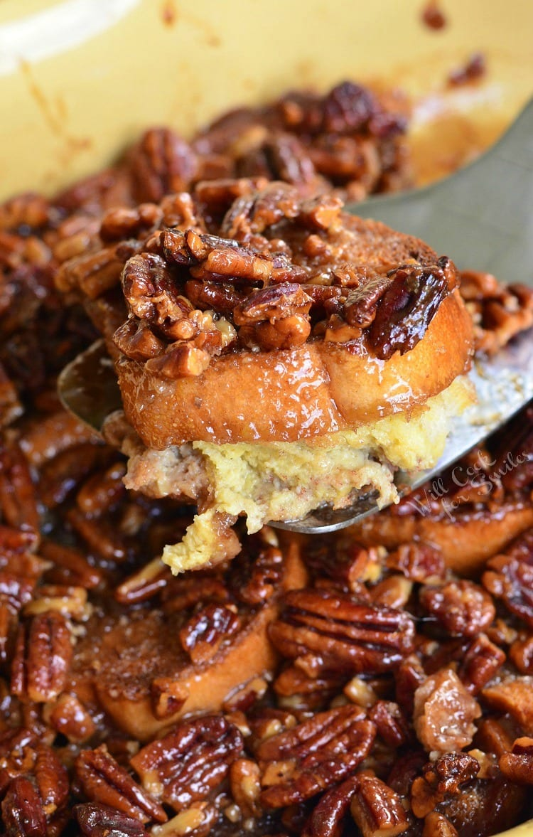 Pecan Pie French Toast Casserole in a yellow casserole dish lifting a piece out with a spatula