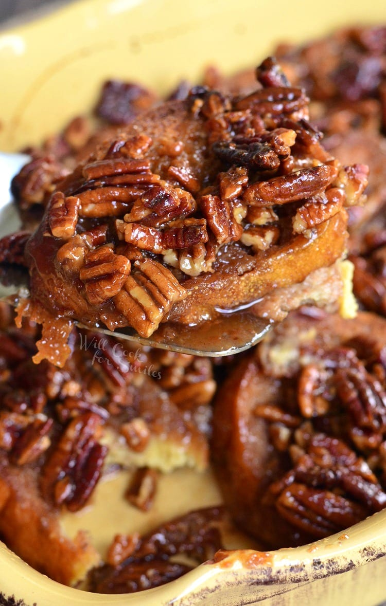 Pecan Pie French Toast Casserole in a yellow casserole dish being lifted out with a spatula